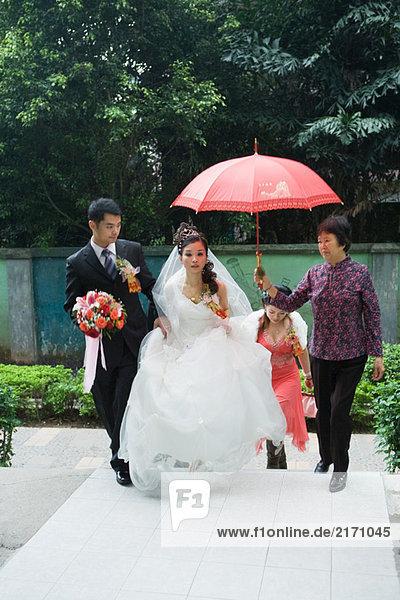 Braut und Bräutigam auf dem Fußweg  Frau mit rotem Sonnenschirm über der Braut