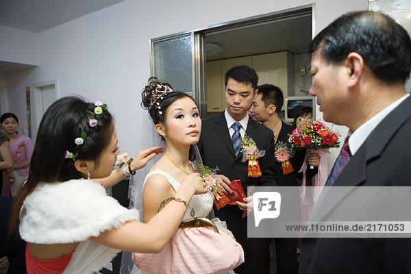 Chinesische Hochzeit  Brautjungfernkette auf der Braut  während andere zusehen.
