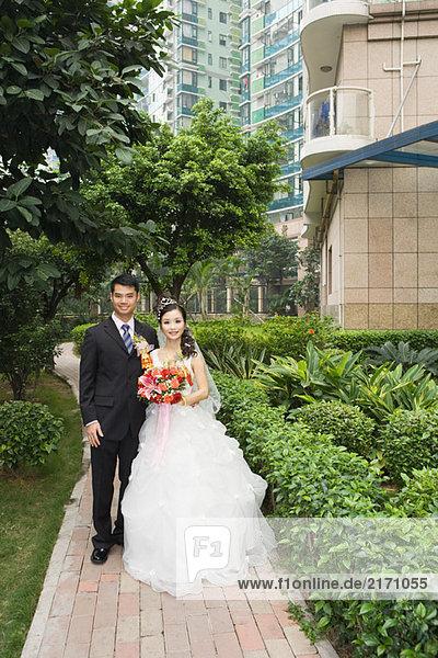 Braut und Bräutigam im grünen Wohnkomplex  Ganzkörperporträt