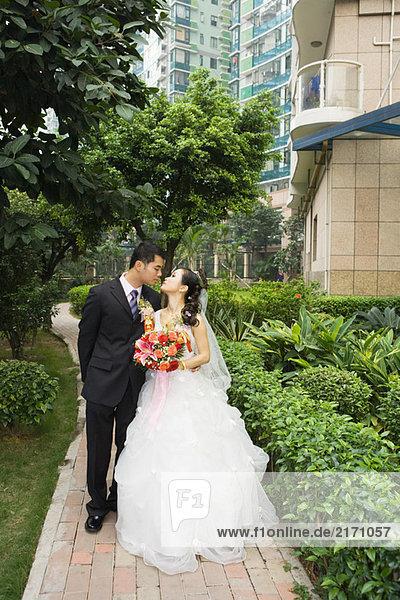 Braut und Bräutigam küssen  Ganzkörperporträt