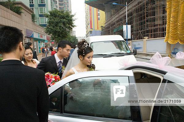 Braut und Bräutigam beim Einsteigen ins Auto