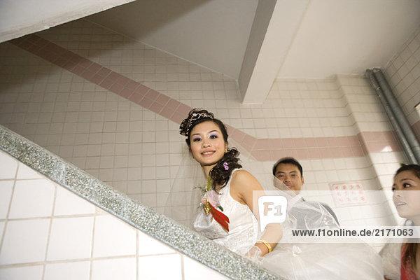 Braut  Bräutigam und Brautjungfer  die die Treppe hinaufgehen.