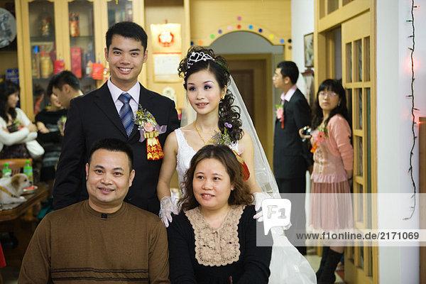Braut und Bräutigam stehen hinter dem Paar  lächelnd  Portrait
