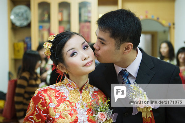 Bride dressed in traditional Chinese clothing  looking at camera as groom kisses her on the cheek