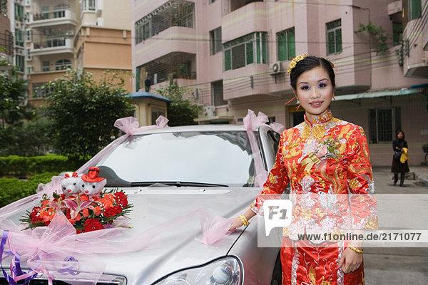 Braut in traditioneller chinesischer Kleidung  neben dem geschmückten Auto stehend  lächelnd vor der Kamera.