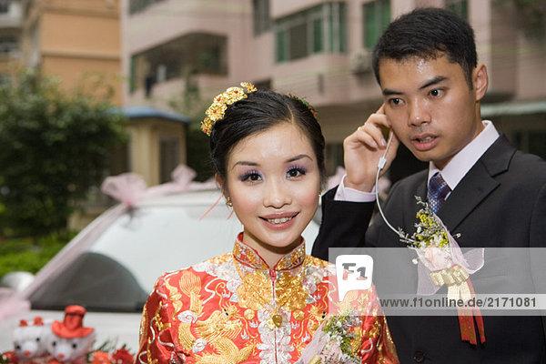 Braut in traditioneller chinesischer Kleidung  lächelnd vor der Kamera  Bräutigam hinter dem Kopfhörer