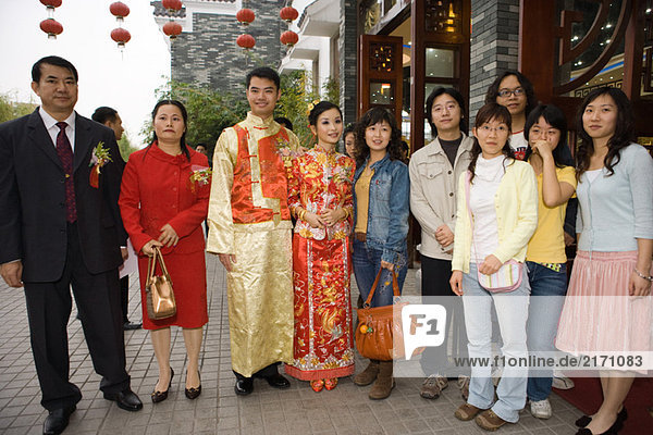 Newlyweds dressed in traditional Chinese clothing  standing with family  group portrait