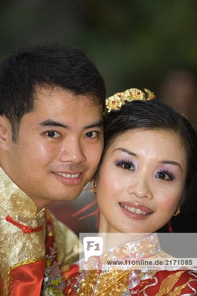 Frischvermählte in traditioneller chinesischer Kleidung  Wange an Wange  lächelnd vor der Kamera