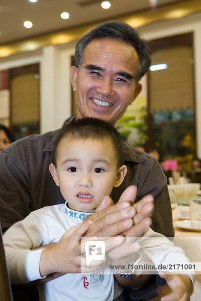 Mann hält Kleinkind auf dem Schoß  klatscht  lächelt vor der Kamera