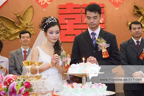 Frischvermählte stehen neben der Hochzeitstorte mit brennender Kerze  Augen geschlossen  gefaltete Hände