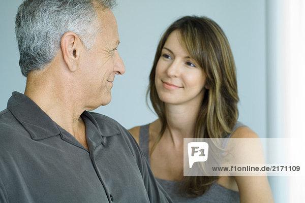 Erwachsener Mann lächelt erwachsene Tochter an  Nahaufnahme