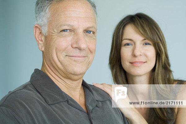Erwachsener Vater und erwachsene Tochter lächelnd vor der Kamera  Porträt