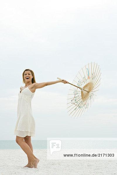Frau hält Sonnenschirm am Strand  volle Länge