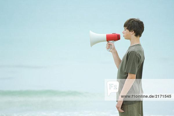 Boy using megaphone  side view