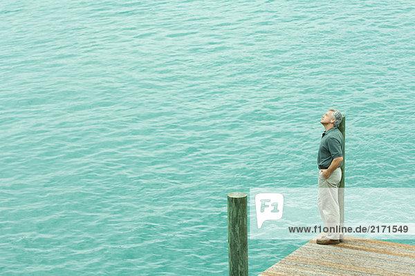Mann steht neben dem Wasser und hört Kopfhörer  schaut weg  Blick in den hohen Winkel