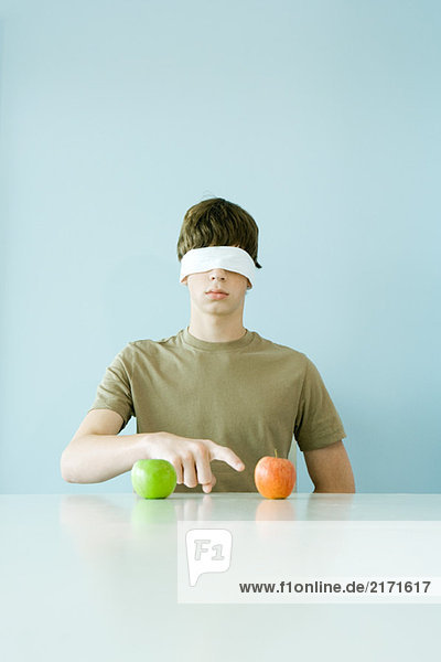 Young male wearing blindfold  pointing to one of two apples