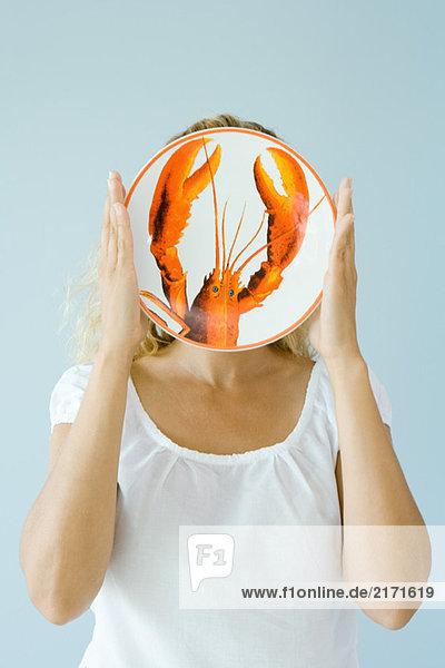 Frau hält Hummerplatte vor dem Gesicht hoch