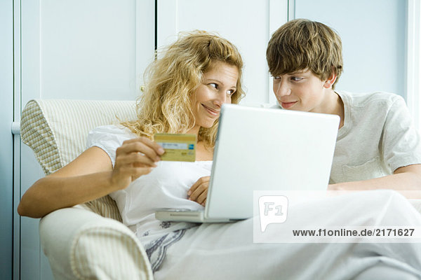 Woman and teen son using laptop  making on-line purchase with credit card