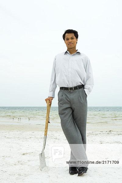 Mann steht am Strand  lehnt sich an die Schaufel  lächelt in die Kamera.