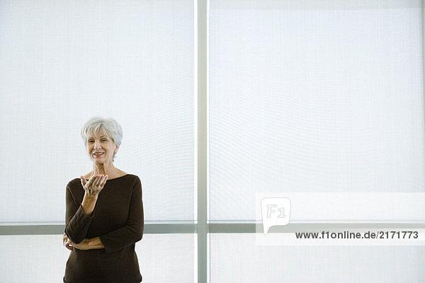 Seniorin stehend mit ausgestreckter Hand  lächelnd vor der Kamera