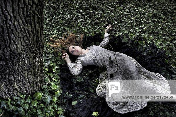 Junge Frau liegt auf einem Bett aus Efeu
