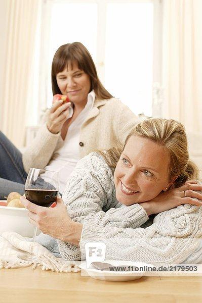 Frau blickt auf ihrer Mutter mit Glas Wein