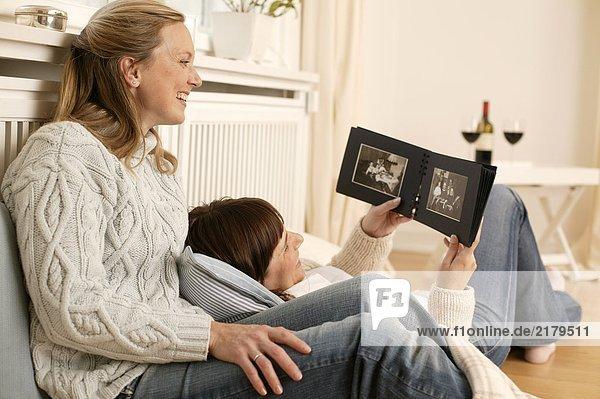 Frau und ihre Tochter Fotoalbum betrachten und lächelnd