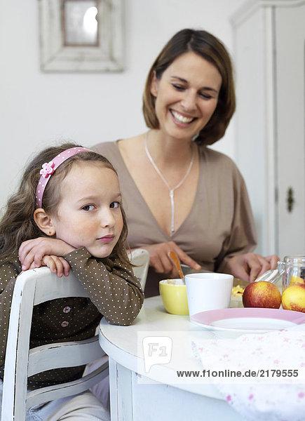 Frau blickt auf ihre Tochter auf Stuhl sitzend