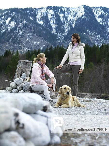 Zwei junge Frauen mit Hund am Flussufer