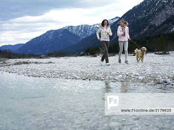 Zwei junge Frauen Joggen mit Hund am Flussufer