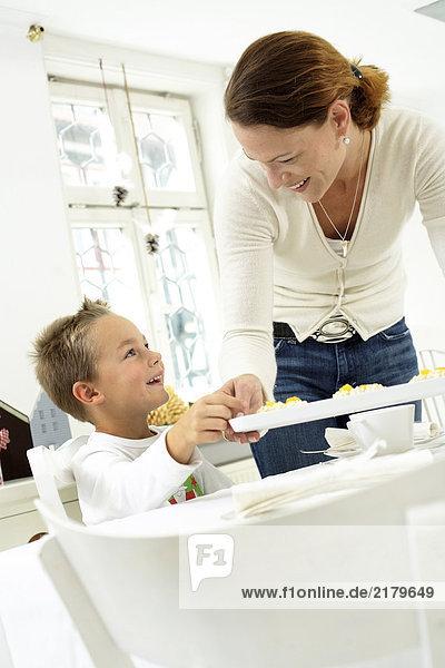 Mitte erwachsen frau mit ihrem Sohn am Tisch essen