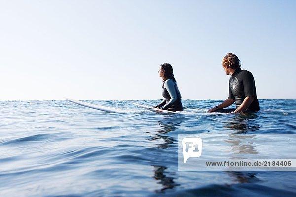 Ein Paar sitzt auf Surfbrettern im Wasser.