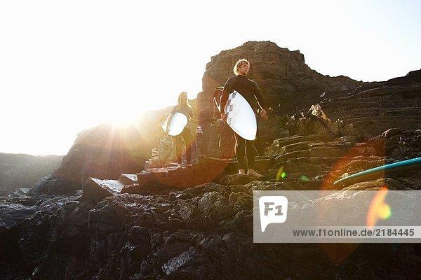 Paar auf großen Felsen stehend mit Surfbrettern.