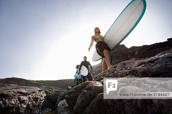 Drei Leute mit Surfbrettern auf großen Felsen lächelnd.