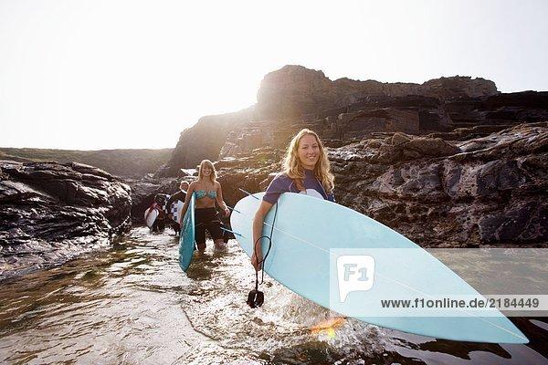 Vier Leute mit Surfbrettern im Wasser lächelnd.