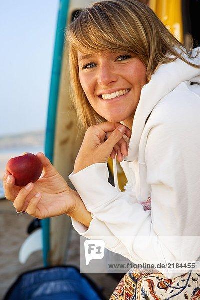 Frau isst einen Apfel mit lächelnden Surfbrettern.
