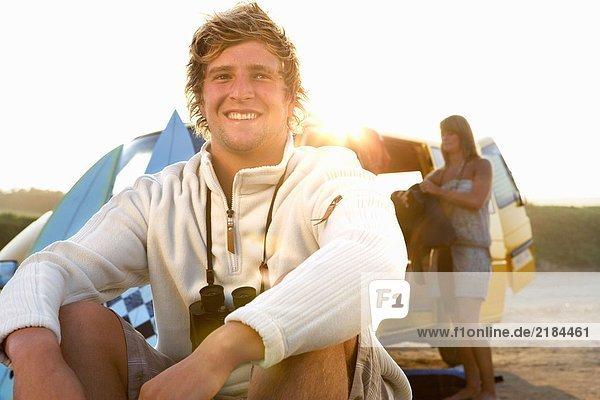 Mann am Strand sitzend lächelnd mit Frau beim Entladen des Lieferwagens am Strand .
