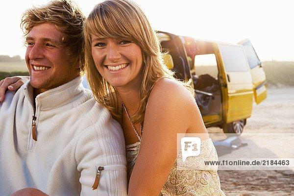 Ein Paar sitzt am Strand und lächelt mit einem Van im Hintergrund.