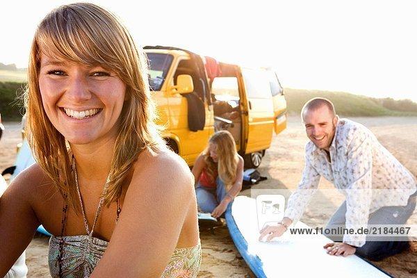 Frau am Strand lächelnd mit ein paar Surfbrettern im Hintergrund.