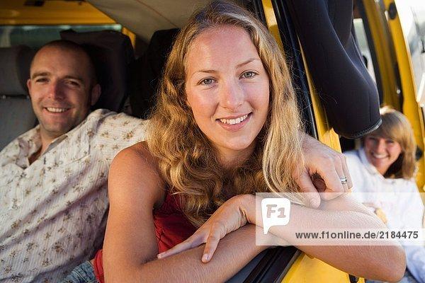 Ein Paar in einem Van lächelt mit einer Frau im Hintergrund.