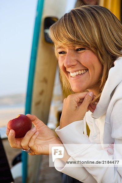Frau isst einen Apfel in der Nähe von Surfbrettern.
