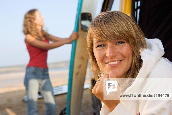 Frau am Strand lächelnd mit einer anderen Frau im Hintergrund  die das Surfbrett hält.