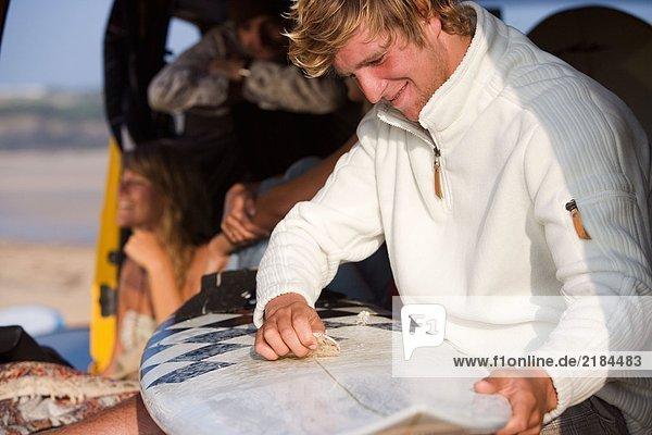 Mann beim Wachsen des Surfbrettes mit lächelndem Paar im Hintergrund.