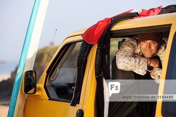 Mann im Van lächelnd mit Surfbrett an der Motorhaube lehnend.