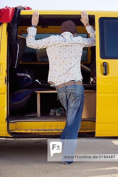 Ein Mann  der in der Tür eines Lieferwagens steht und reinschaut.