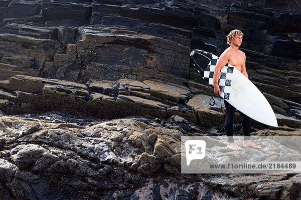 Mann steht mit Surfbrett auf großen Felsen.
