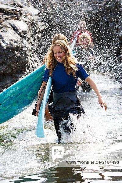 Vier Leute spritzen mit Surfbrettern an großen Felsen und lächeln.