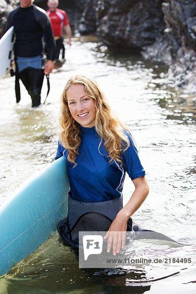 Drei Leute tragen Surfbretter durchs Wasser und lächeln.