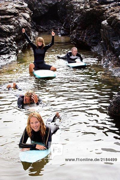 Vier Leute haben Spaß auf Surfbrettern im Wasser und lächeln.