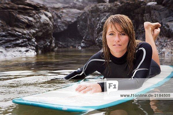 Frau liegt auf dem Surfbrett im Wasser.